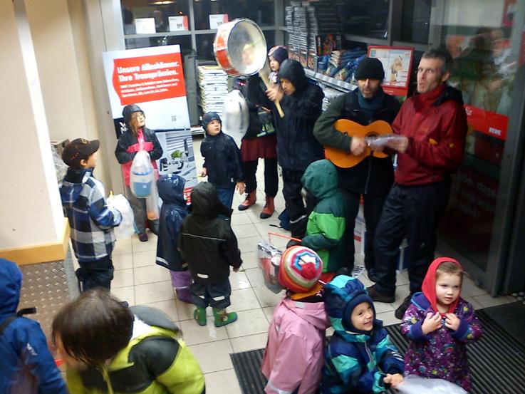 Kinder und Eltern der Kita singen Martinslieder im REWE.